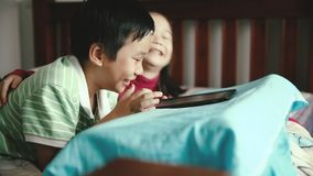 Asian children using digital tablet. Shift focus. Asian children using digital tablet. Happily sister smiling and cheering her brother. Cute boy playing games stock video footage