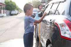 Asian children are using water hose to washing car royalty free stock photo