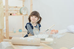 Asian children waiting her mother for preparing the dough Royalty Free Stock Images