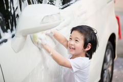 Asian children washing car Royalty Free Stock Photo