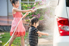 Asian children washing car Royalty Free Stock Image