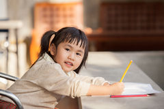 Asian children with yellow pencil in hand doing school home work Royalty Free Stock Images