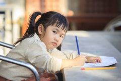 Asian children with yellow pencil in hand doing school home work Stock Photos