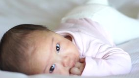 Asian Chinese baby rolling on bed and looking curious stock video footage