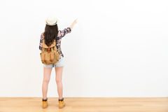 Asian chinese backpacker pointing to the copyspace. Asian chinese backpacker standing on the wooden floor and hand gesture pointing to the copyspace on the white Stock Images