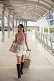 Chinese Female traveler in Bangkok city. Asian Chinese beautiful female traveler walking and pulling luggage in modern city with sky with urban Bangkok Royalty Free Stock Images