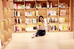 Asian Chinese beautiful pretty cute woman girl student Teenager read book in bookstore library. She wears white shirt blue jeans read book engrossed concentrate royalty free stock image
