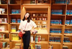 Asian Chinese beautiful pretty young cute woman girl student Teenager read book in bookstore library smile spend her pastime. Asian Chinese beautiful pretty cute Royalty Free Stock Photos