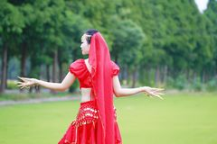 Brightness of dance Asian Chinese belly dancer in red dress Royalty Free Stock Photo