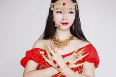 Graceful Asian Chinese belly dancer in White background. Asian Chinese beauty belly dancer, dancing in White background, wear a red India stytle belly dance stock image