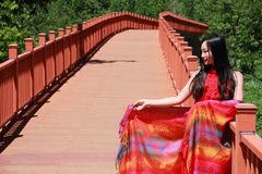 Asian Chinese beauty in red dress enjoy peaceful and happy life at Yunnan Lugu walking marriage bridge Royalty Free Stock Image