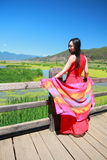 Asian Chinese beauty in red dress enjoy peaceful and happy life at Yunnan Lugu walking marriage bridge. Asian Chinese beauty in red dress enjoy peaceful and Stock Image