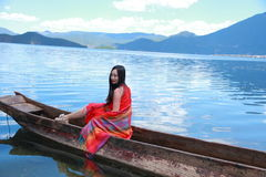 Asian Chinese beauty in red dress with red scraf on head, sit in Mosuo special canoe at  Yunnan Lugu lake, enjoy free time Stock Photo