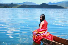 Asian Chinese beauty in red dress with red scraf on head, sit in Mosuo special canoe at  Yunnan Lugu lake, enjoy free time Stock Image