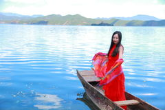 Asian Chinese beauty in red dress with red scraf on head, Stand in Mosuo special canoe at  Yunnan Lugu lake, enjoy free time Royalty Free Stock Photo