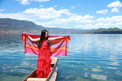 Asian Chinese beauty in red dress with red scraf on head, stand in Mosuo special canoe at  Yunnan Lugu lake, enjoy free time Royalty Free Stock Photos