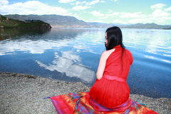 Asian Chinese beauty in red dress with red scraf on head, at  Yunnan Lugu lake, enjoy free time Royalty Free Stock Photography