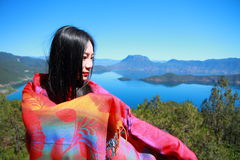 Asian Chinese beauty in red dress with red scraf on head, at  Yunnan Lugu lake, enjoy free time Royalty Free Stock Images