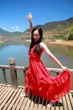 Asian Chinese beauty in red dress with red scraf on head, at  Yunnan Lugu lake, enjoy free time Royalty Free Stock Photo