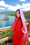 Asian Chinese beauty in red dress with red scraf on head, at  Yunnan Lugu lake, enjoy free time Stock Images
