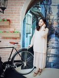 Beautiful sweet Chinese girl in an old alley of shanghai. Asian Chinese beauty sit on an old bike, in an old alley of shanghai, sweet smile on face Royalty Free Stock Photos