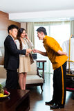 Asian Chinese bell boy or porter receiving tip. Baggage porter or bellboy or page receiving tip for delivering the suitcase of guests to the hotel room or suite stock photography