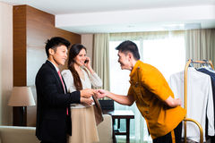 Asian Chinese bell boy or porter receiving tip. Baggage porter or bellboy or page receiving tip for delivering the suitcase of guests to the hotel room or suite royalty free stock photo