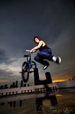 Asian Chinese Bicycle Guy doing a stunt on rooftop. Picture of BMX flatland cyclist doing a stunt on a rooftop. Picture is useful for Gen X, Gen Y description of royalty free stock photography
