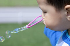 Asian Chinese boy blowing soap bubbles stock image