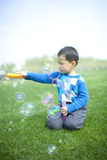 Asian Chinese boy blowing soap bubbles stock photos