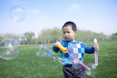 Asian Chinese boy blowing soap bubbles Royalty Free Stock Photos