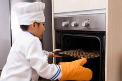 Asian Chinese Boy in white chef uniform Baking Cookies Royalty Free Stock Photos