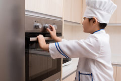 Asian Chinese Boy in white chef uniform Baking Cookies Royalty Free Stock Photography