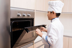 Asian Chinese Boy in white chef uniform Baking Cookies Stock Images