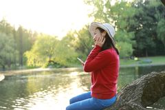Asian Chinese careless girl is listening to music sit on a tree by a river in spring autumn park. Portrait of a Asian Chinese free woman reading book sit on a stock photography