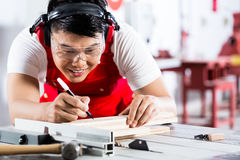 Asian Chinese Carpenter cutting wood with saw Stock Photos