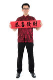 Asian Chinese cheongsam male holding couplet. Full body Asian man with Chinese traditional cheongsam or tang suit holding couplet, the Chinese word means Stock Photography