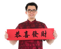 Asian Chinese cheongsam man holding couplet. Asian man with Chinese traditional cheongsam or tang suit holding couplet, the Chinese word means congratulations Royalty Free Stock Photography