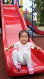 Asian chinese child at the bottom of the slide Royalty Free Stock Images