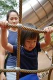 Asian Chinese Child climbing rope obstacle course watched by adult stock photos