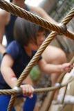 Asian Chinese Child climbing rope obstacle course watched by adult stock photo