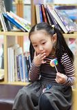 Asian chinese child licking a lollipop. Asian chinese child licking an unhealthy rainbow lollipop In front of the bookcase royalty free stock photo