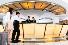 Asian Chinese couple arriving at hotel front desk. Asian Chinese women and men arriving at front desk or reception of luxury hotel in business clothes with Stock Images