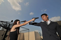 Asian chinese couple trying to kill each other. Asian Chinese couple with guns pointing at each other Royalty Free Stock Image