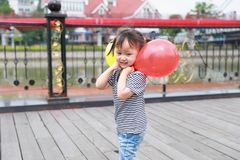 Asian Chinese cute naughty lovely adorable girl play with balloon and have fun outdoor in summer park happy smile walk on street. A little Asian Chinese girl Stock Images