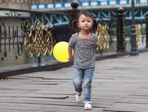 Asian Chinese cute naughty lovely adorable girl play with balloon and have fun outdoor in summer park happy smile walk on street. A little Asian Chinese girl Royalty Free Stock Photography