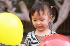 Asian Chinese cute naughty lovely adorable girl play with balloon and sit by a tree have fun outdoor in summer park happy smile. A little Asian Chinese girl Stock Image