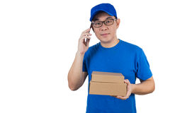 Asian Chinese delivery guy in uniform talking over mobile phone Stock Images
