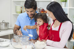 Asian Chinese Family Cooking in Home Kitchen. Asian Chinese family, men & women parents and young girl child daughter cooking, baking, making cakes in home Royalty Free Stock Images
