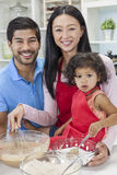 Asian Chinese Family Cooking in Home Kitchen. Asian Chinese family, men & women parents and young girl child daughter cooking, baking, making cakes in home Stock Photo
